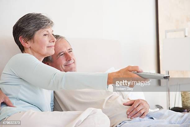 Ein altes Paar vor dem Fernseher im Bett zusammen