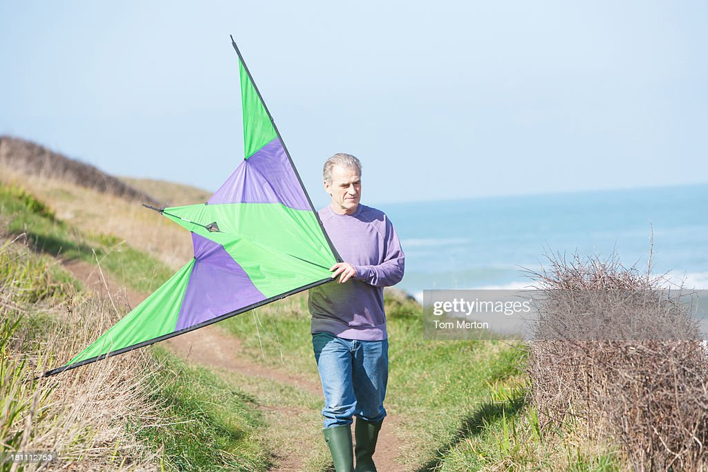a senior man with a kite at the beach : Stock Photo