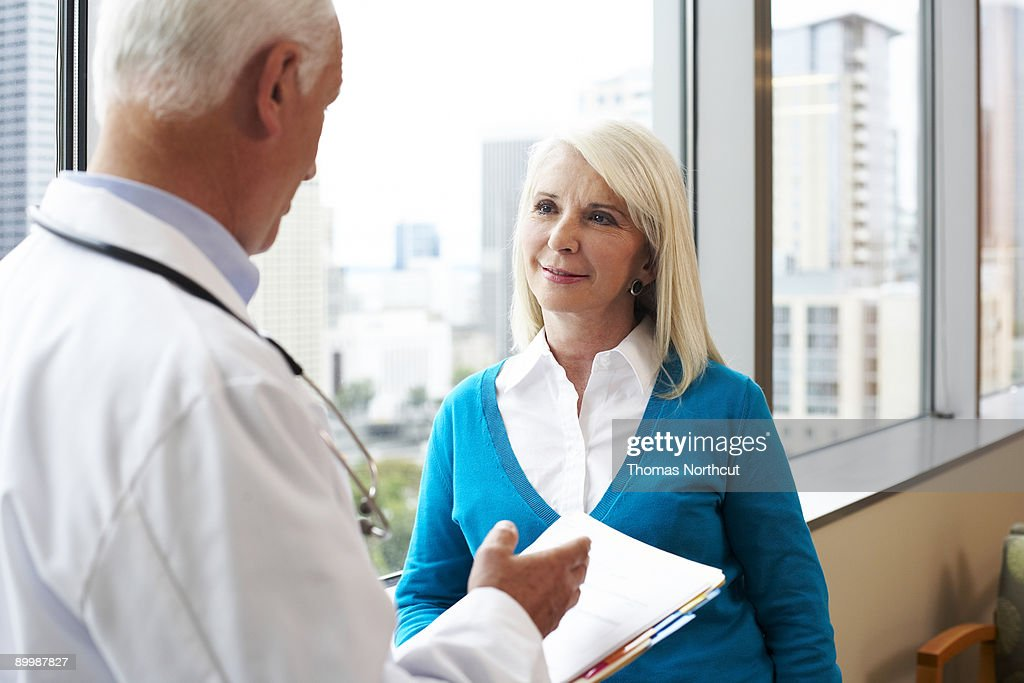 a senior woman listens carefully to her doctor : Stock Photo