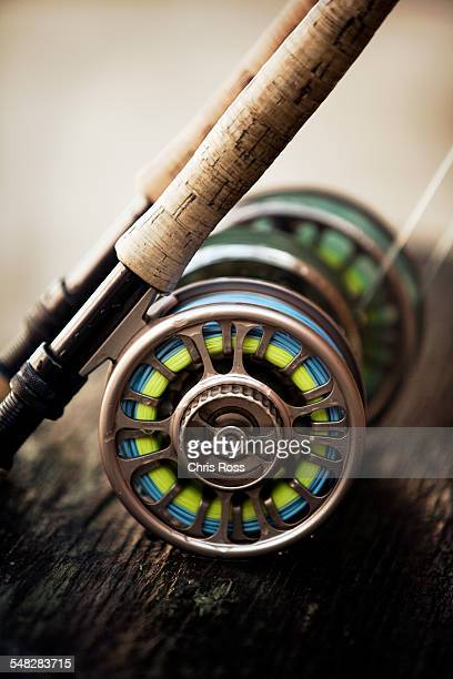 a short focus shot of fly reel resting on wooden plank