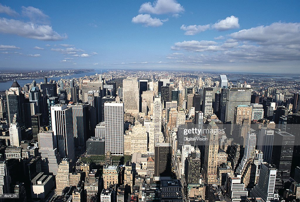 a shot of New York city from above with its skyscrapers and blue sky streaked with clouds : Stock Photo