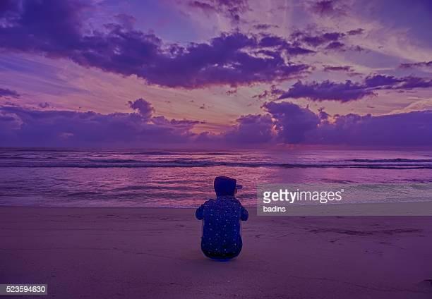 a silhouette man sit on enjoy a golden sunrise near at beach.