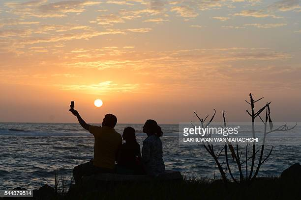 a Sri Lankan family takes a 'selfie' at sunset on a beach in Colombo on July 3 2016 / AFP / LAKRUWAN WANNIARACHCHI