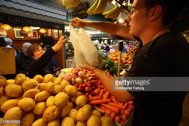 A a stall holder sells vegetables to a customer at Bolton Market as figures for the Uk inflation rate show that it continues to slow on August 17...