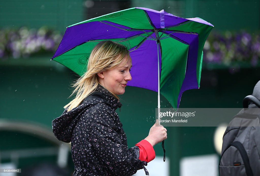 a supporter hides under her broken umbrella on day three of the Wimbledon Lawn Tennis Championships at the All England Lawn Tennis and Croquet Club on June 29, 2016 in London, England.