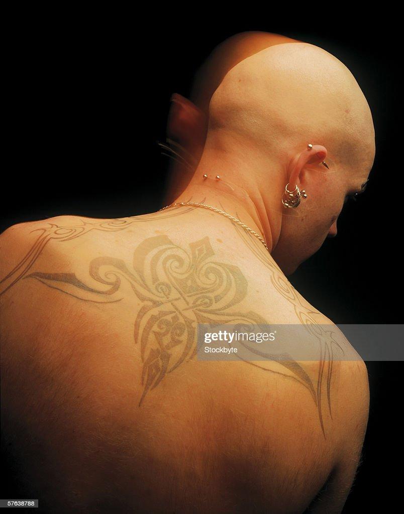 a tattoo across a bald man's back : Stock Photo