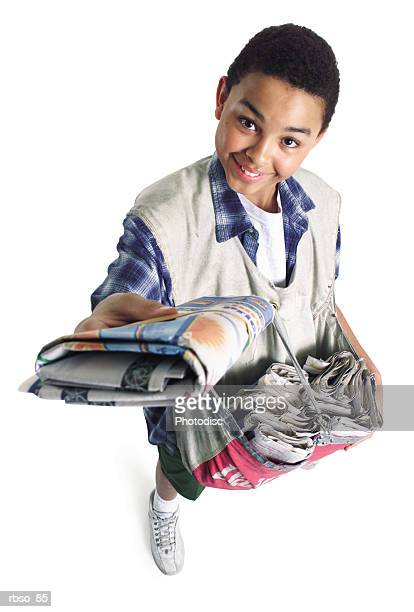 a teenage african american paper boy holds a newspaper up as he smiles up to the camera