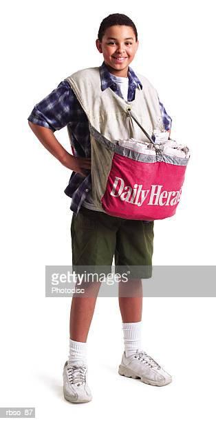 a teenage african american paper boy smiles as he wears a bag of newspapers