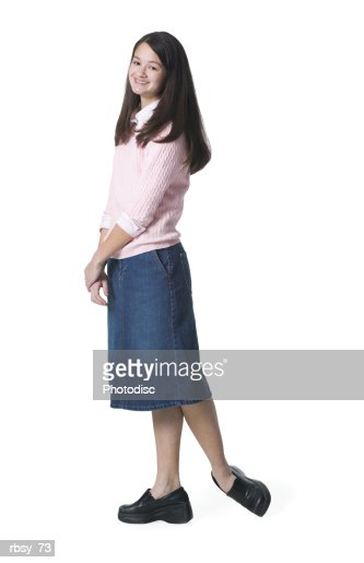 A Teenage Asian Girl In A Jean Skirt And Pink Sweater Kicks Her Foot Up And