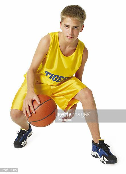 a teenage caucasian male basketball player in a yellow uniform dribbles the ball under his legs