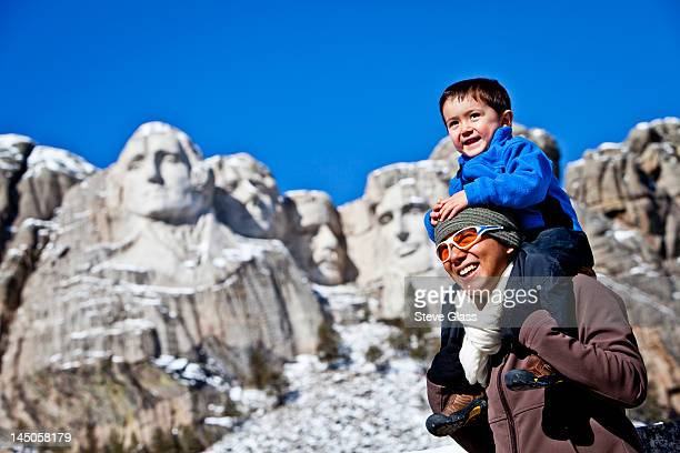 a thirty year old, Japanese-American woman stands in front of Mt Rushmore National Memorial while carrying on her shoulders her 2.5 year old son