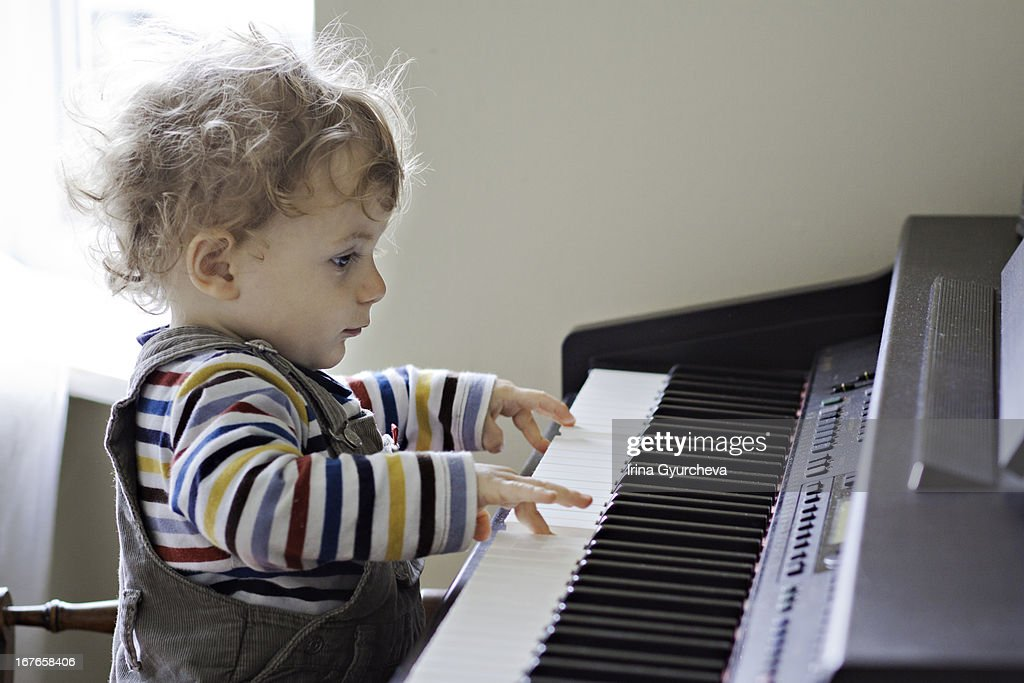 a toddler playing the piano : Stock Photo