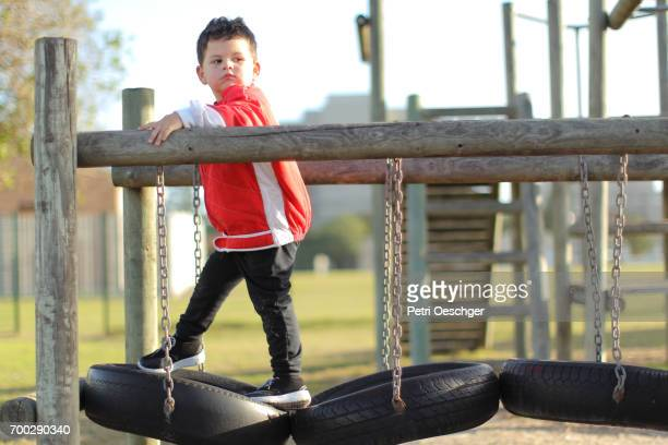 a Toddler plays alone on the jungle gym.