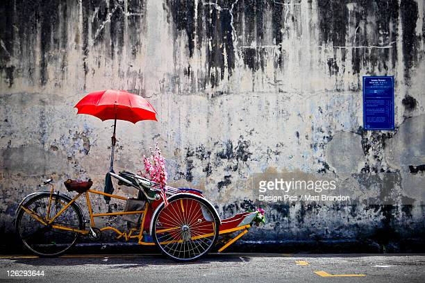 a traditional penang trishaw sits in front of an old weathered wall