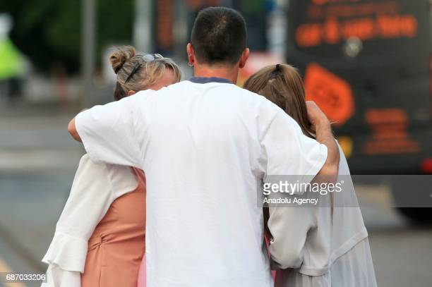a waiting man hugs his wife and daughter outside the Manchester Arena stadium in Manchester United Kingdom on May 23 2017 A large explosion was...