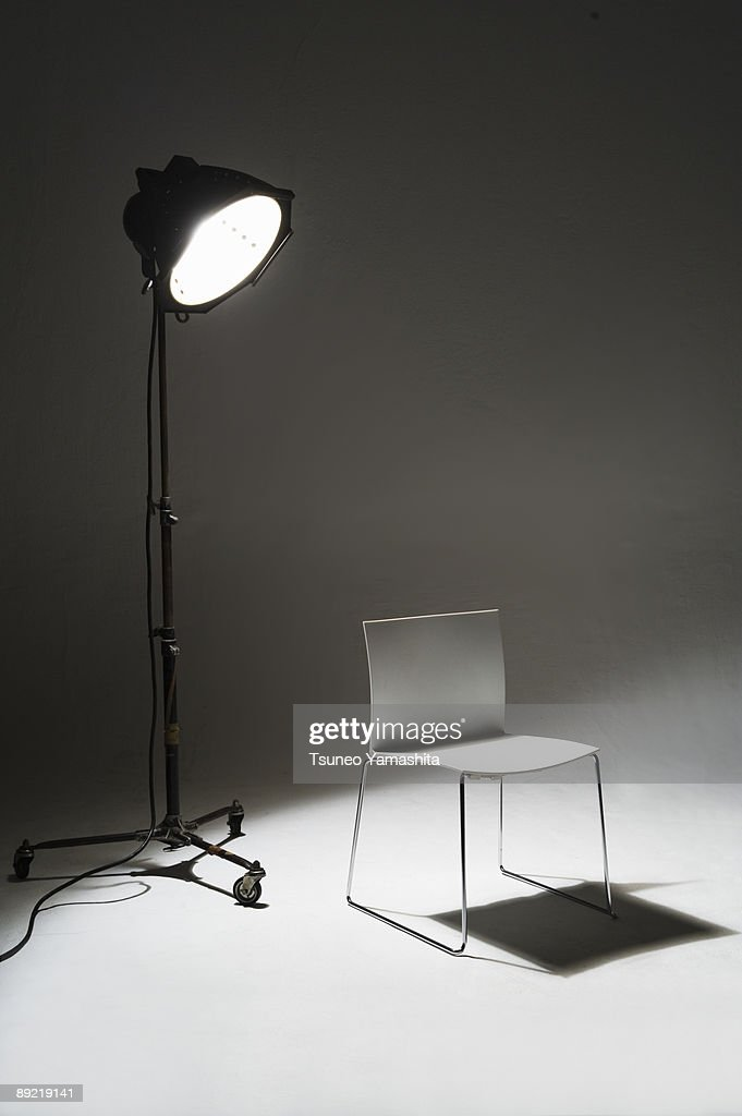 a white chair that stands in the spotlight
