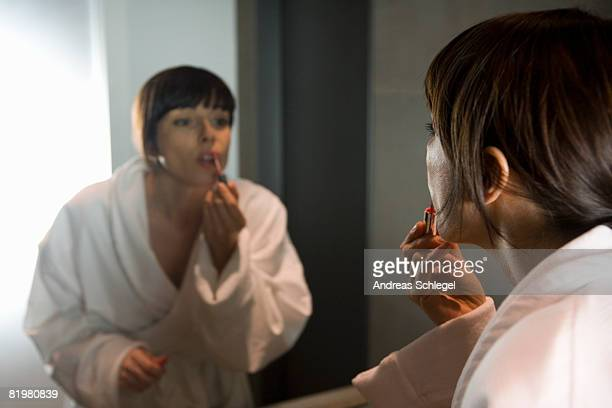 a woman applying lip gloss in a mirror
