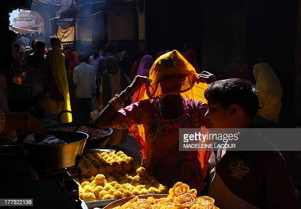 CONTENT] a woman buying ladous sweets made with milk and sugar in a market street