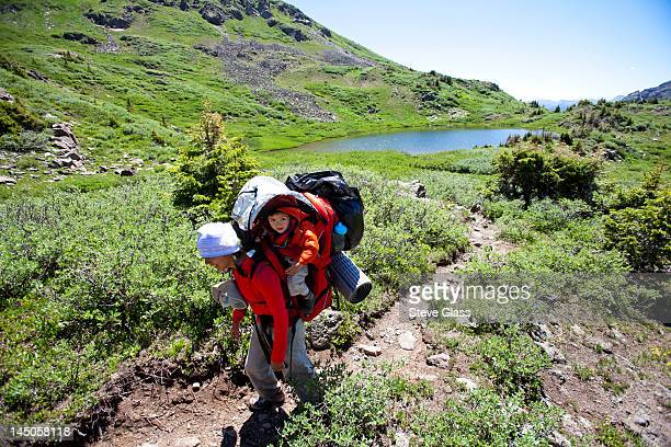 a woman hikes above tree line on Williams Creek Trail (trail number 587) while carrying her son in her backpack.