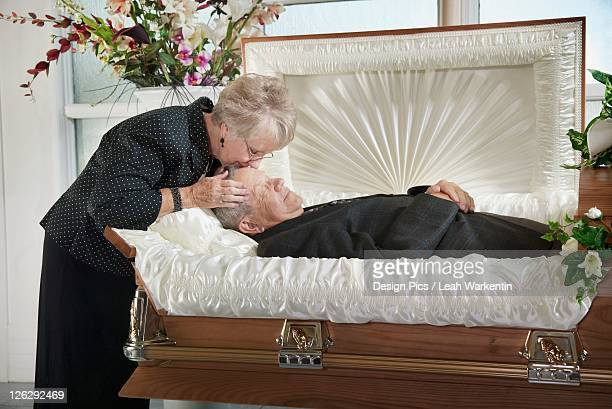 a woman kisses the head of her dead husband