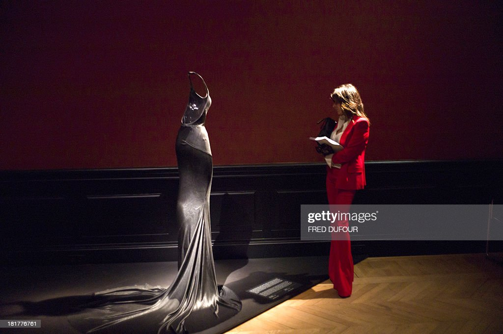 a woman looks at a dress of French designer Azzedine Alaia during his exhibition at the Palais Galliera, on September 25, 2013, in Paris. AFP PHOTO / FRED DUFOUR