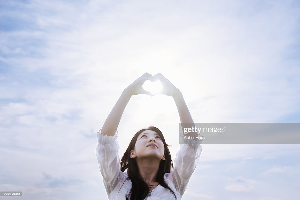 a woman making a heart by hands under a sky : Stock Photo