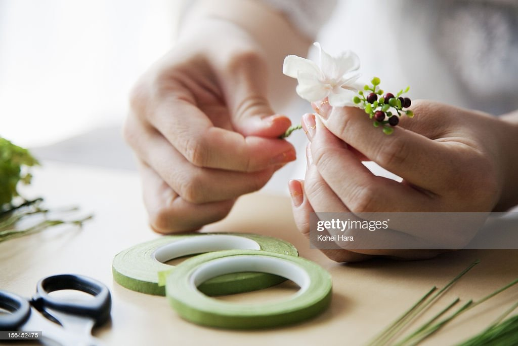 a woman making artificial flowers into corolla : Stock Photo