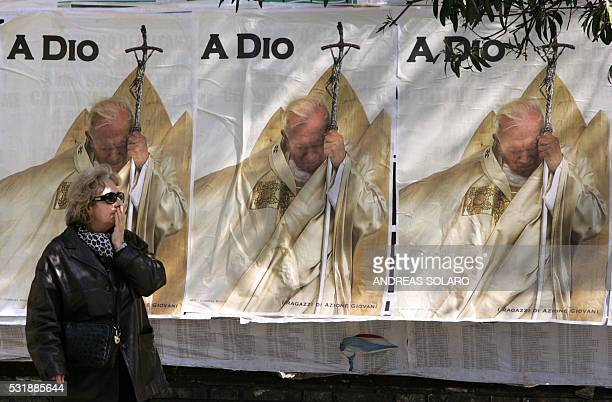 a woman passes by some posters using the picture of French AFP photographer Gabriel Bouys 07 april 2005 in Rome The picture which won a World Press...