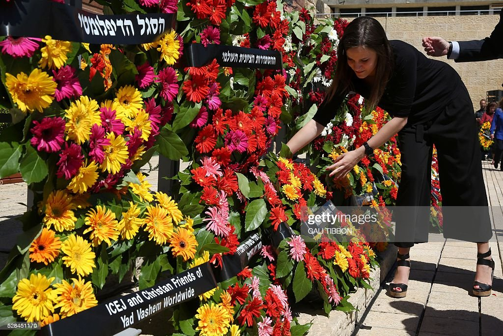 a woman places a wreath during a ceremony marking the annual Holocaust Remembrance Day at the Yad Vashem Holocaust Memorial in Jerusalem on May 5, 2016. The state of Israel marks the annual Memorial Day commemorating the six million Jews murdered by the Nazis in the Holocaust during World War II. / AFP / GALI