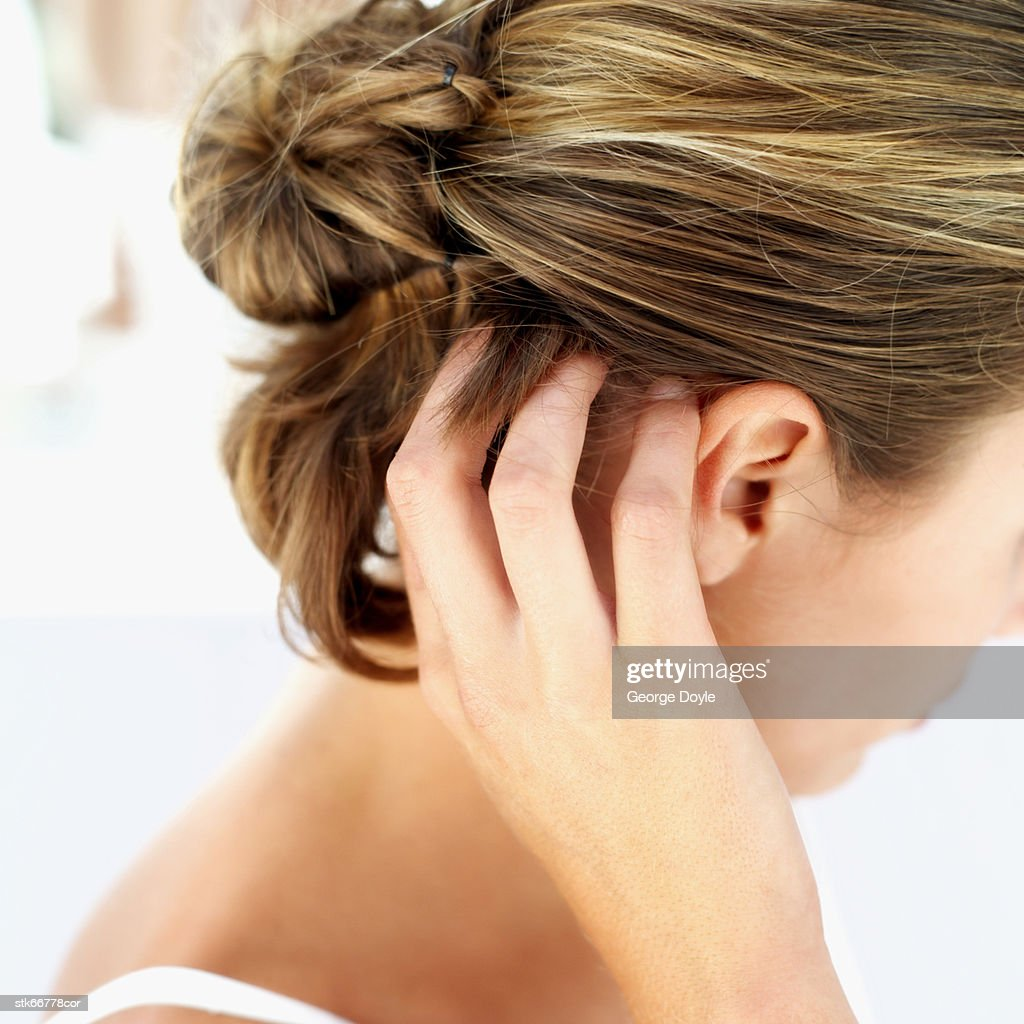 a woman scratching her scalp : Stock Photo