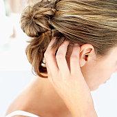 a woman scratching her scalp