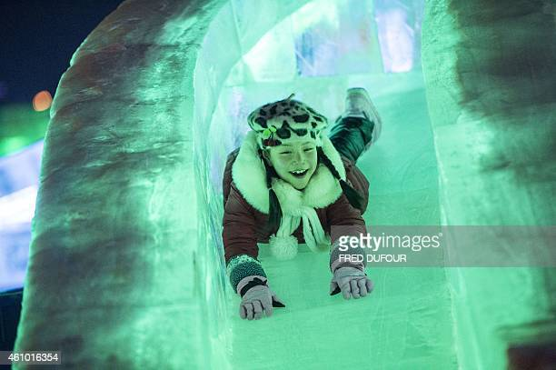a woman slides at the China Ice and Snow World on January 4 2015 on the eve of the opening ceremony of the 16th Harbin International Ice and Snow...