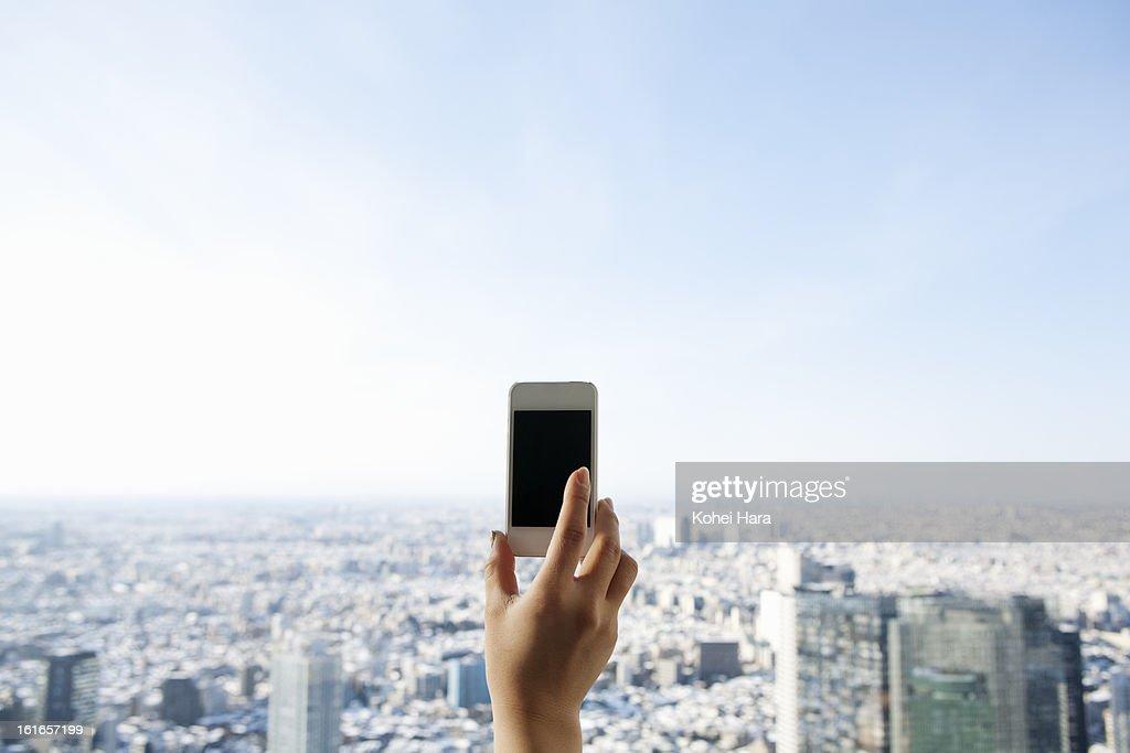 a woman using a smart phone in a skyscraper : Stock Photo