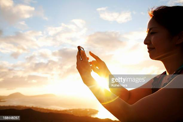 a woman using a smart phone on the mountain