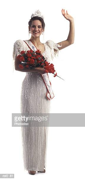 a young adult female beauty pageant contestant with flowers and a tiara waves at the camera