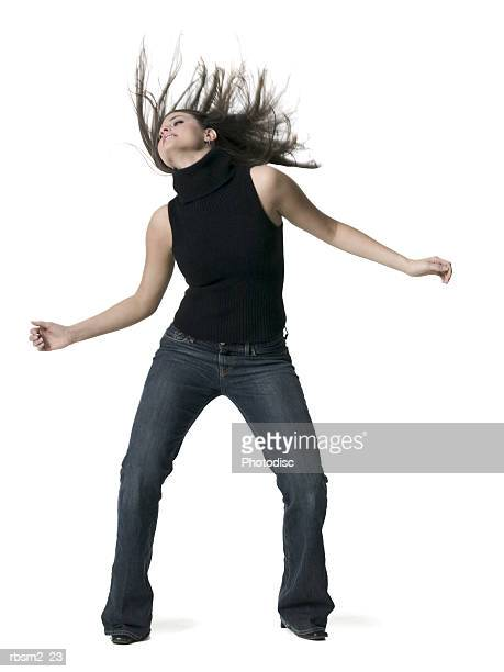 a young adult female in jeans and a black sweater dances and tosses her hair wildly