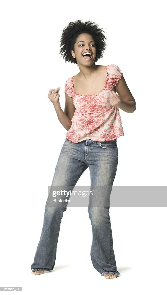 a young adult female in jeans and a floral shirt dances around and smiles : Stock Photo