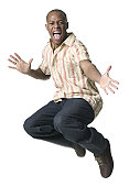 a young adult male in jeans and a striped shirt jumps up playfully into the air
