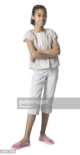 a young african american female child in tan pants and a patterned shirt folds her arms and smiles