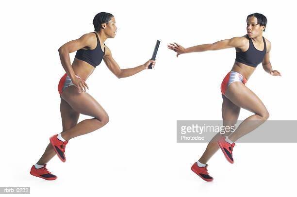 a young african american female runner passes the baton to a strikingly similar looking teammate