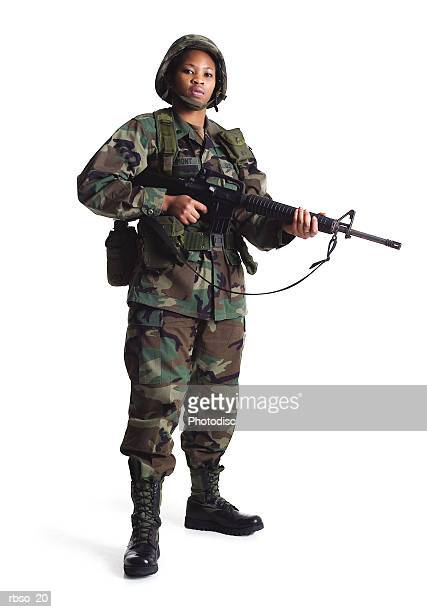 a young african american female soldier stand in fatighues with her gun
