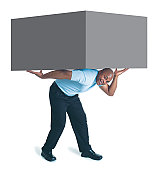 a young african american male in black pants and a blue shirt holds a giant box up with his arms and back