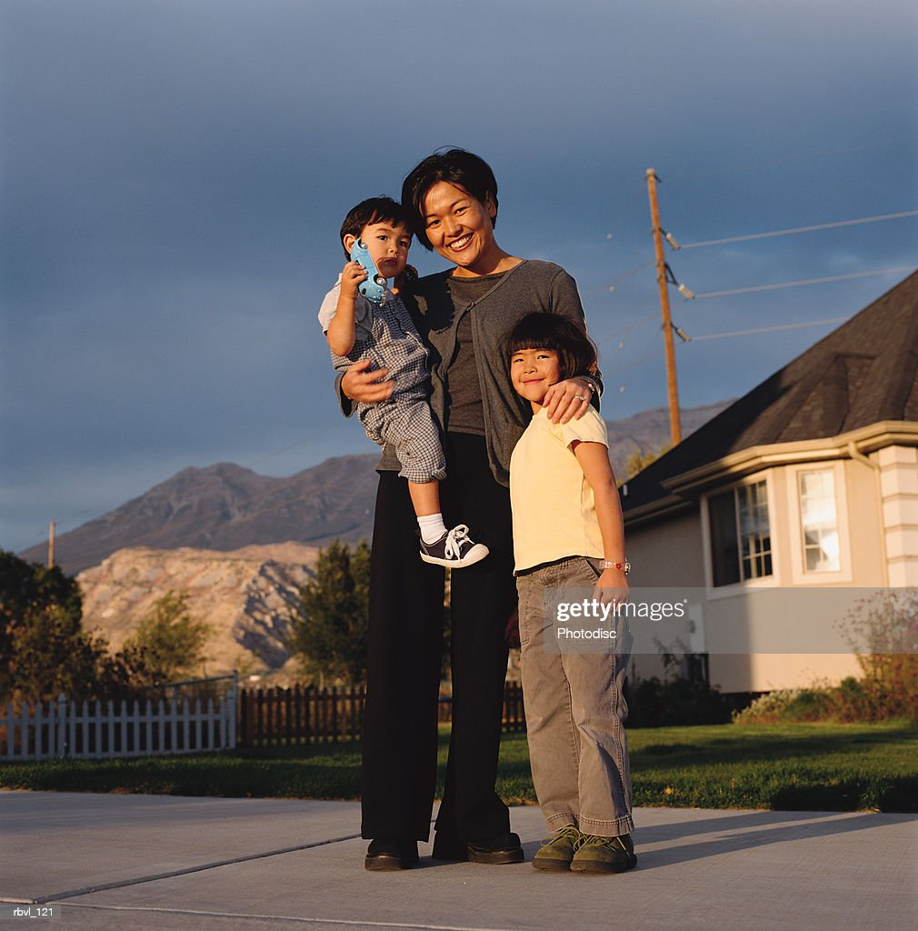 a young asian mother wearing dark pants and blouse is holding her toddler son and has her arm around her little girl as they smile towards the camera : Stock Photo