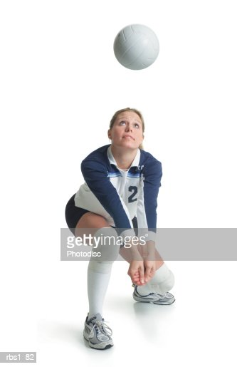 a young attractive caucasian female volleyball player in a blue and white jersey kneels forward preparing to hit a ball flying towards her
