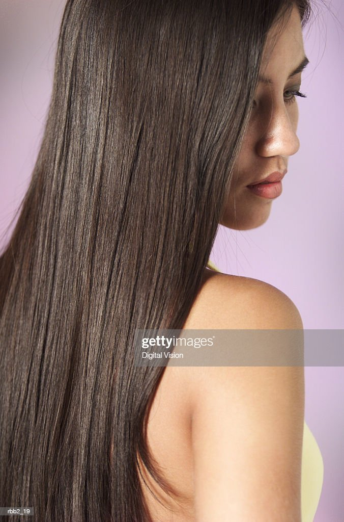 a young attractive ethnic girl with beautiful long dark hair looks down past her shoulder : Stock Photo