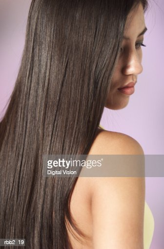 a young attractive ethnic girl with beautiful long dark hair looks down past her shoulder