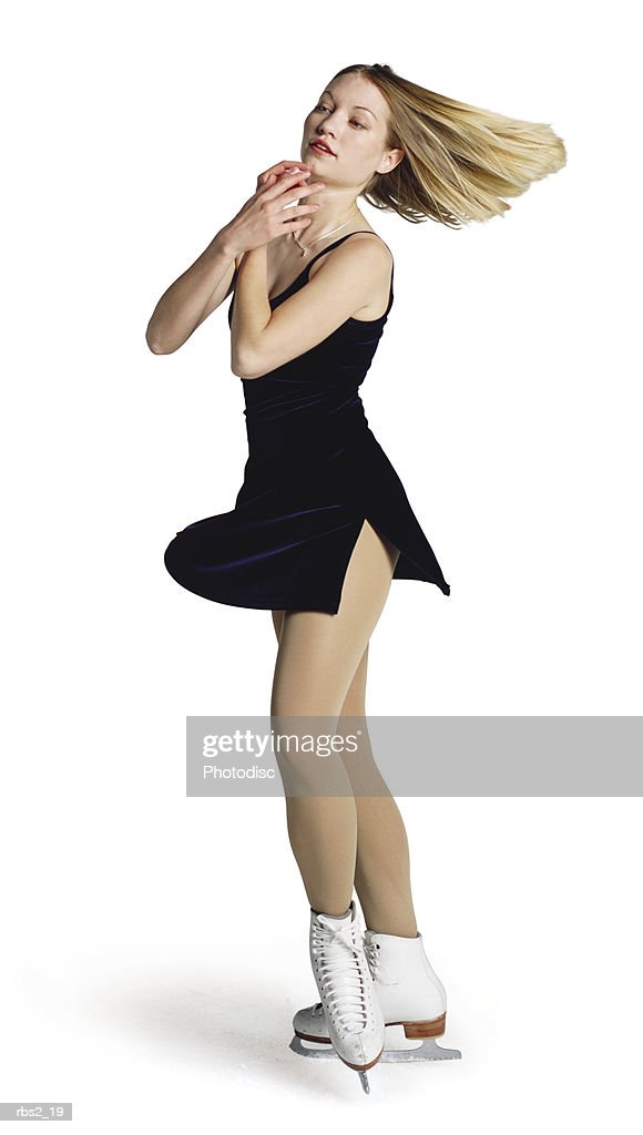 a young blonde caucasian female ice skater in a dark blue outfit spins and skates on the ice : Stock Photo