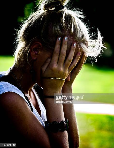 a young blonde female with her hands on her head looking upset