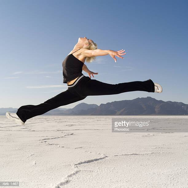 a young blonde woman dressed in black jumps through the air in a desert setting