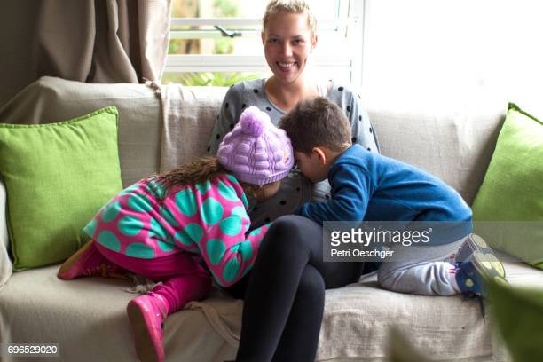 a Young boy and girl bonding with their pregnant mother on the couch.
